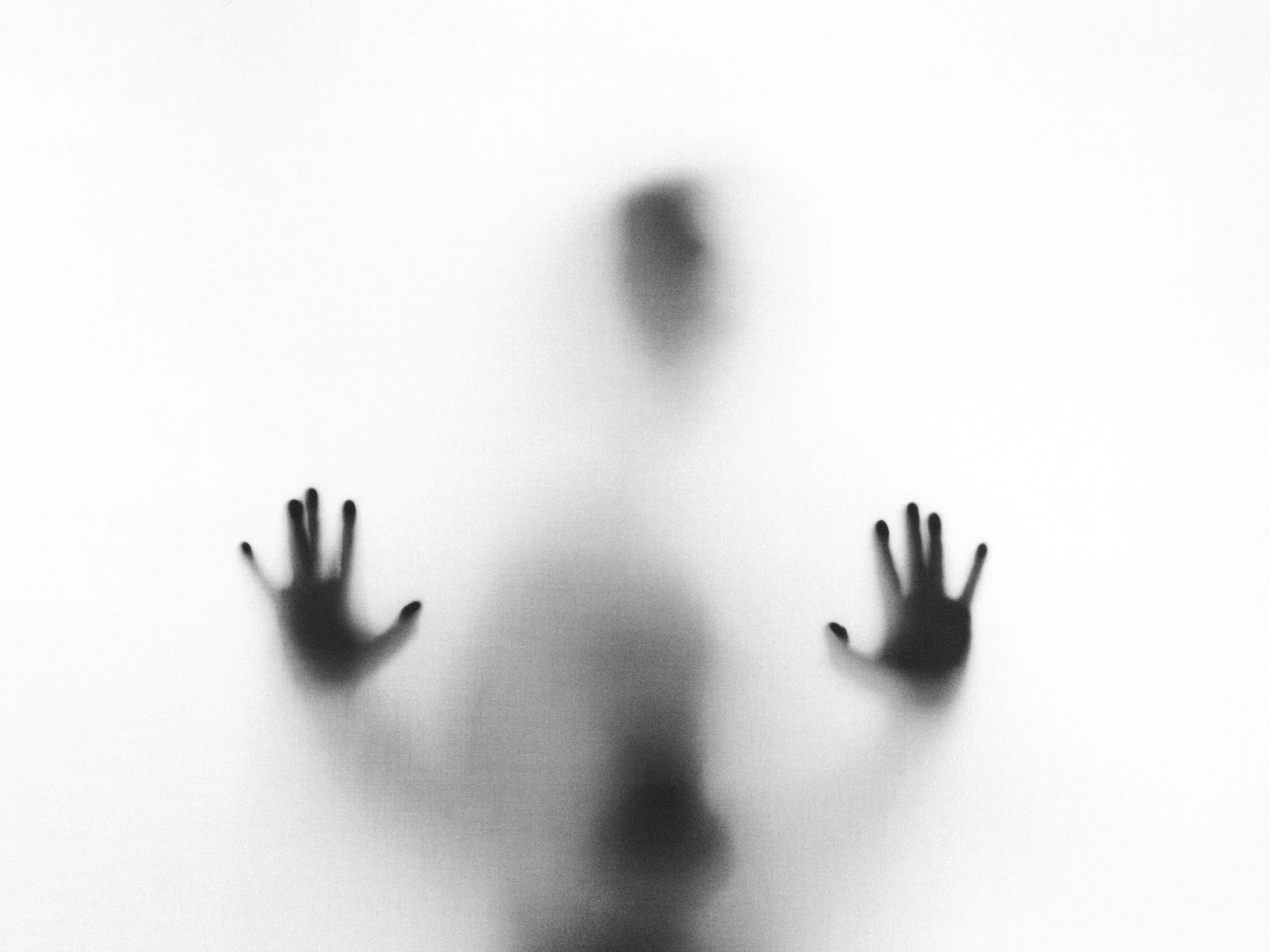 man standing behind glass surrounded by fog with only hands visible on glass