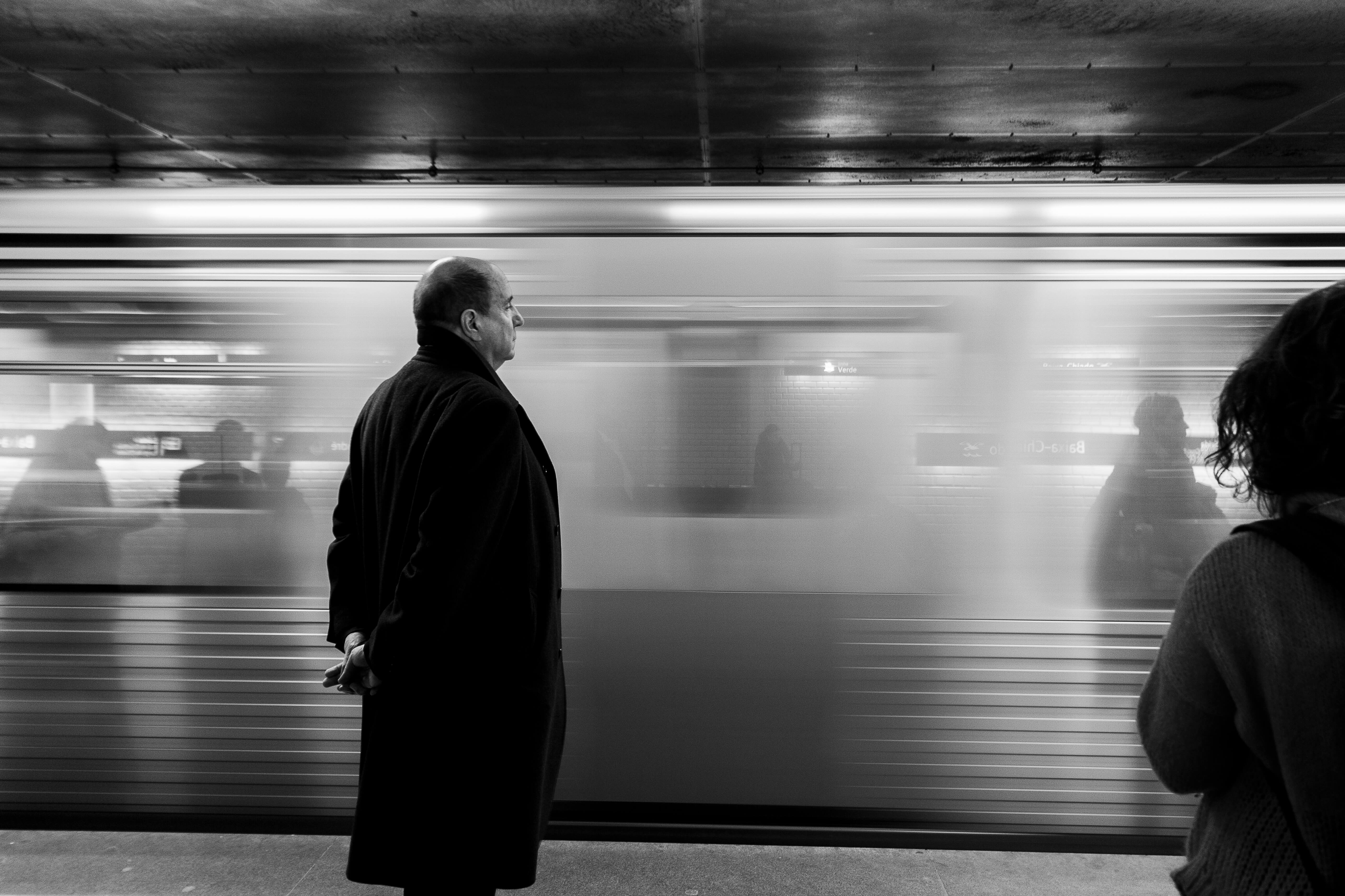 life goes on picture of a man standing on the subway as a train goes past