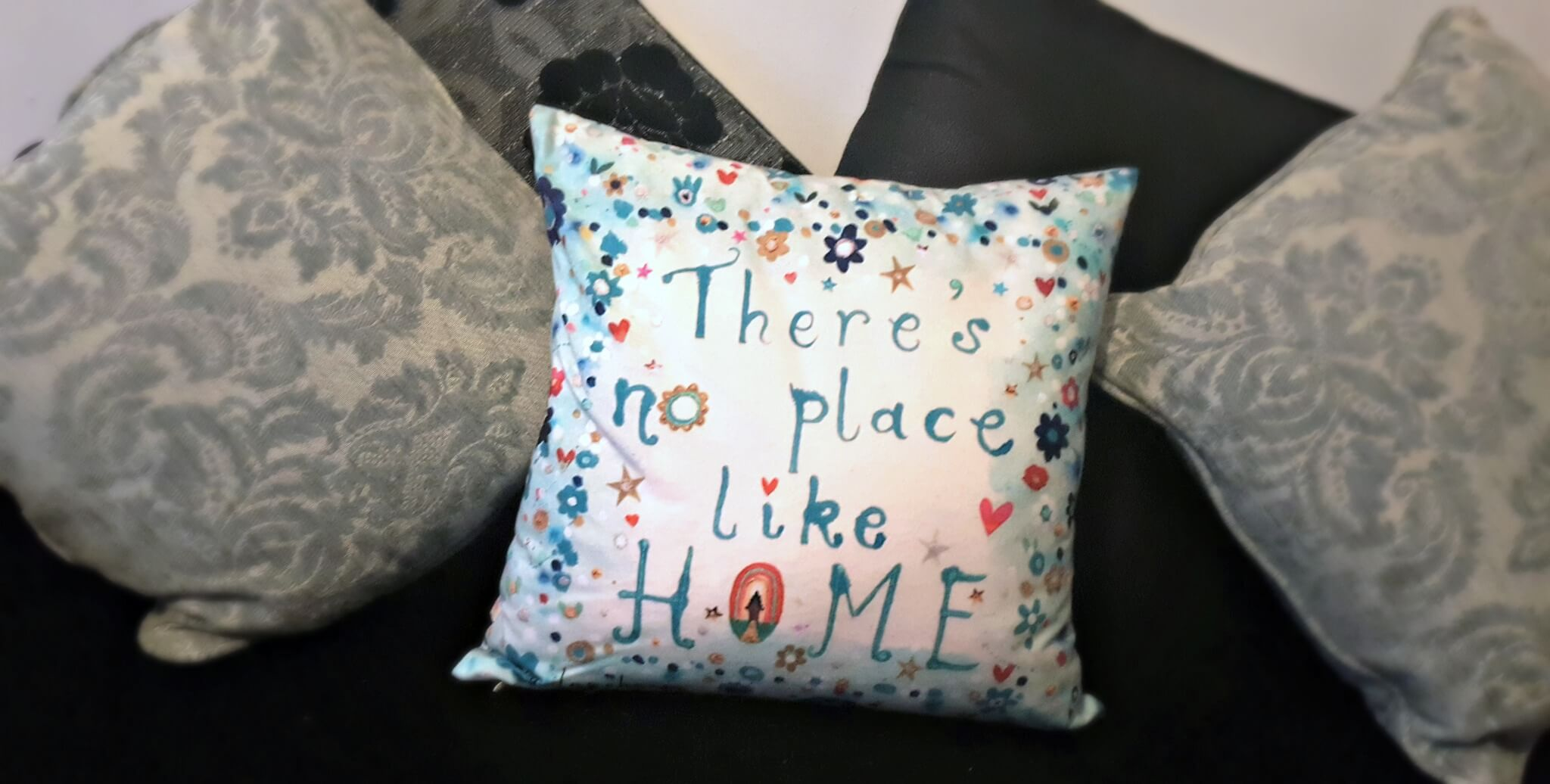 selection of cushions showing one saying there's no place like home