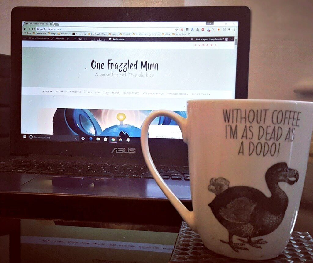 why do I blog picture of a cup in front of a laptop displaying blog logo