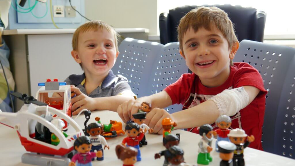 donate to alder hey campaign two boys playing with toys in hospital environment