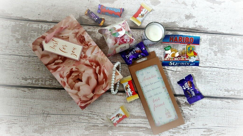 happy aunties day bags featuring small gifts and sweets on a wooden floor background