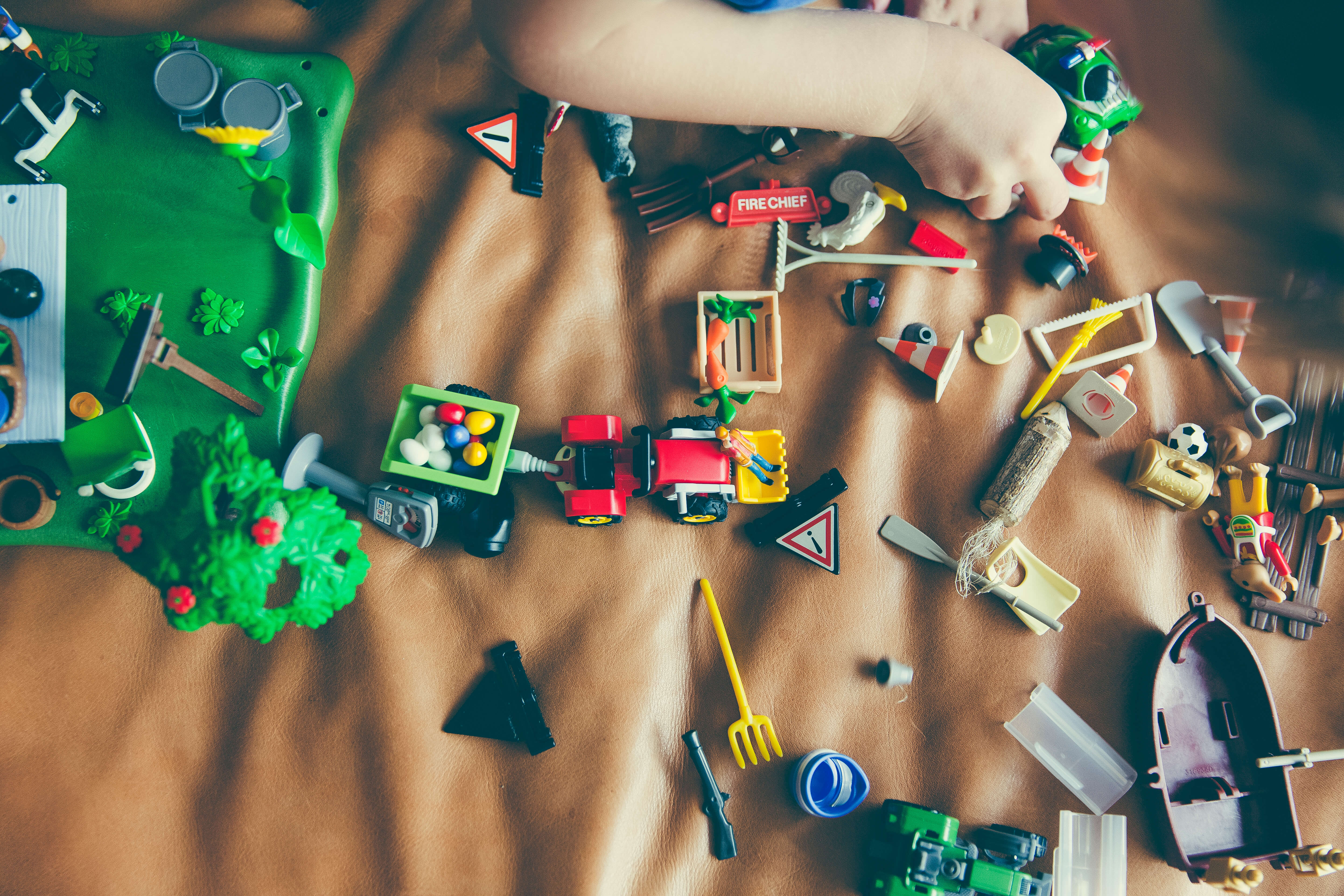 toys sread out on a carpet as a child plays with them making learning fun