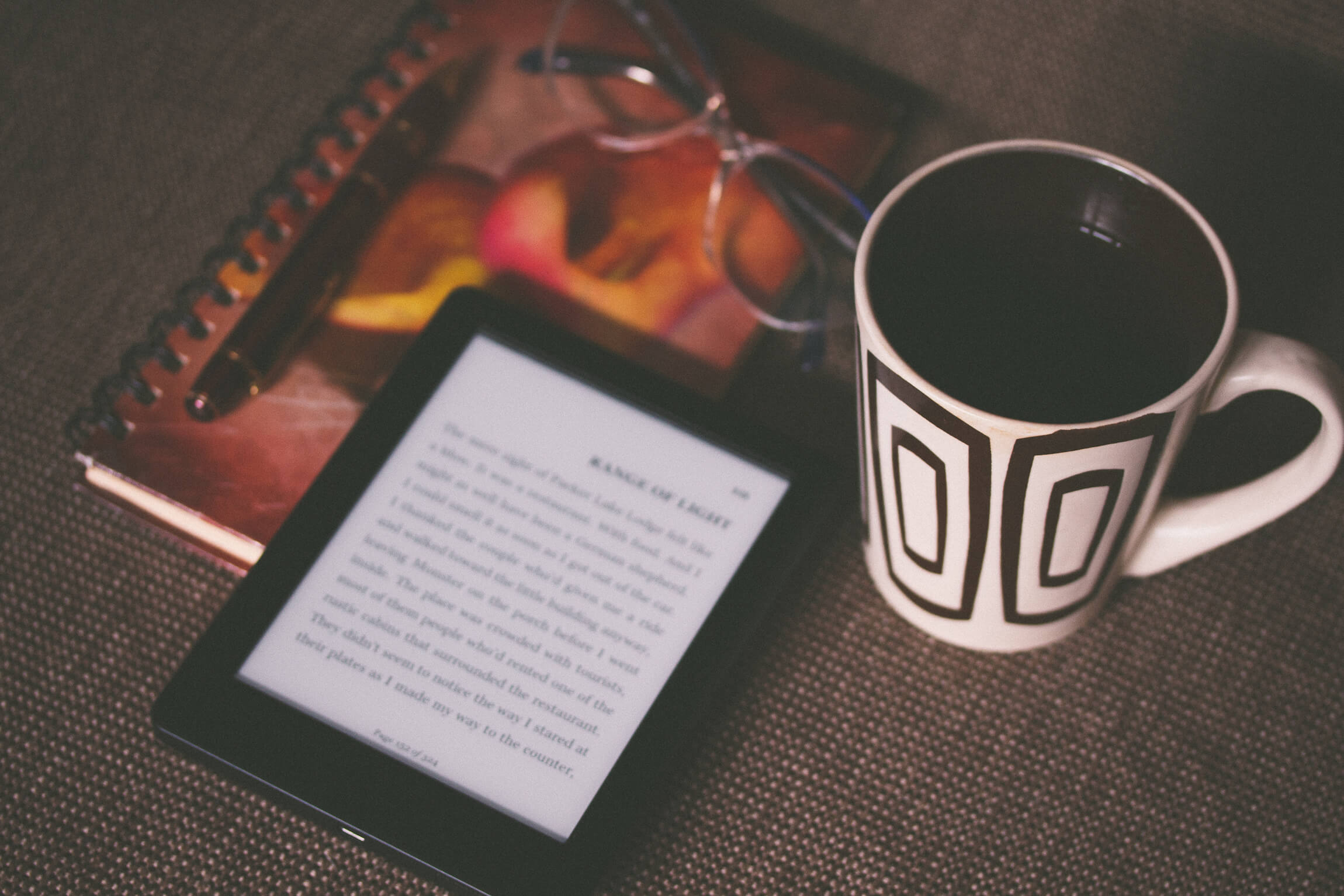 e reader on s notepoad with a mug for a post on free YA ebooks