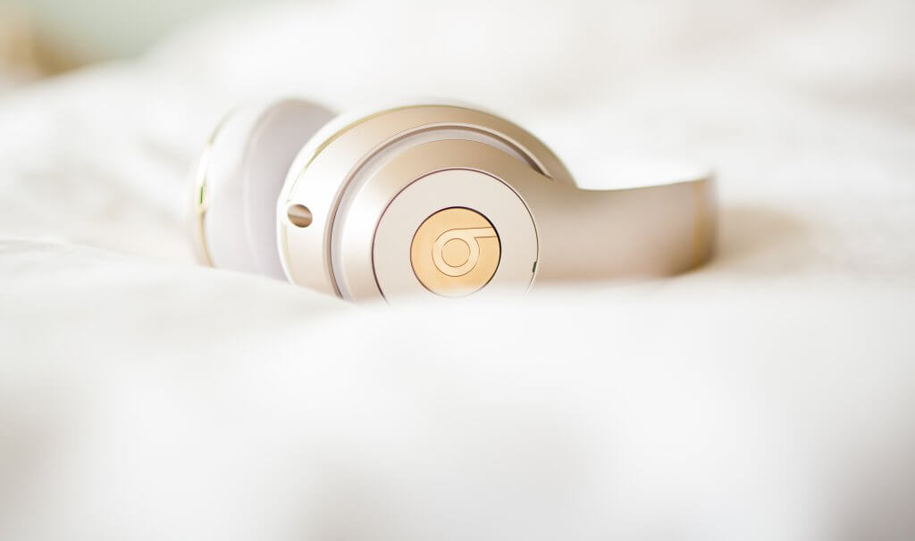headpohnes on white blanket for listening to audio books for beating boredom blues