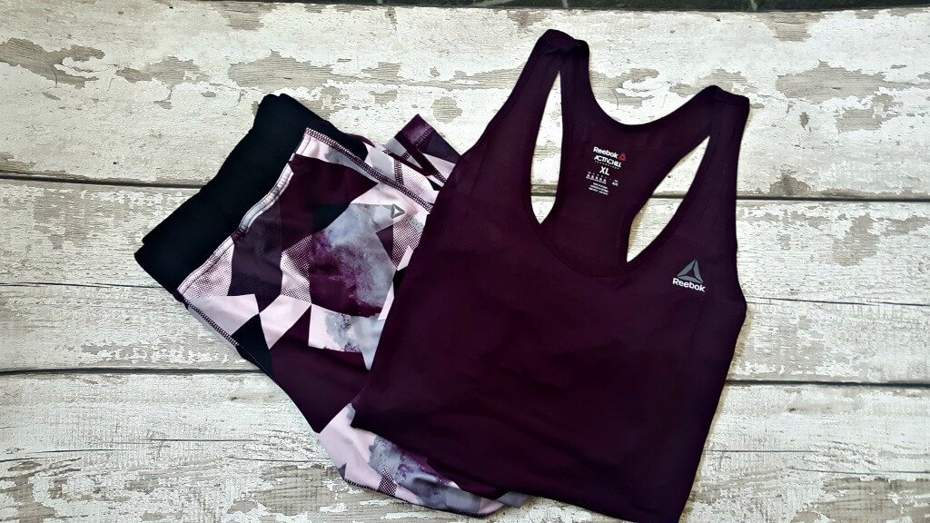 flatlay of a plus size active wear outfit in deep purple on a background
