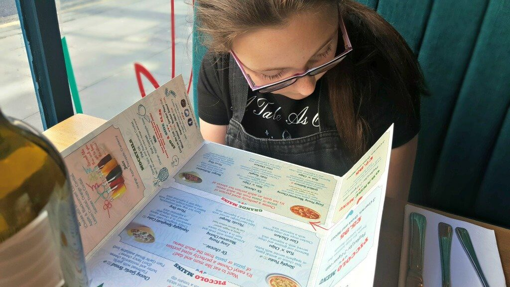 girl reading menu at bella italia using discounted gifts cards from zeek