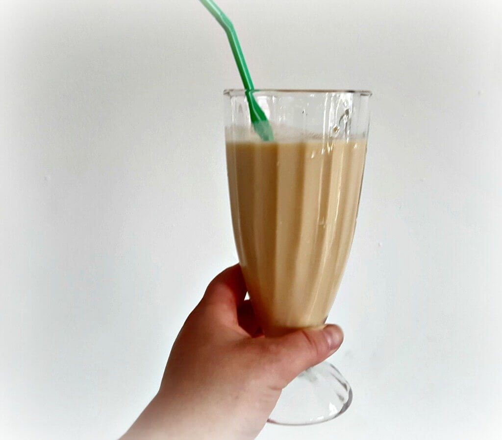 smoothie on a tall glass with a green straw against a white background