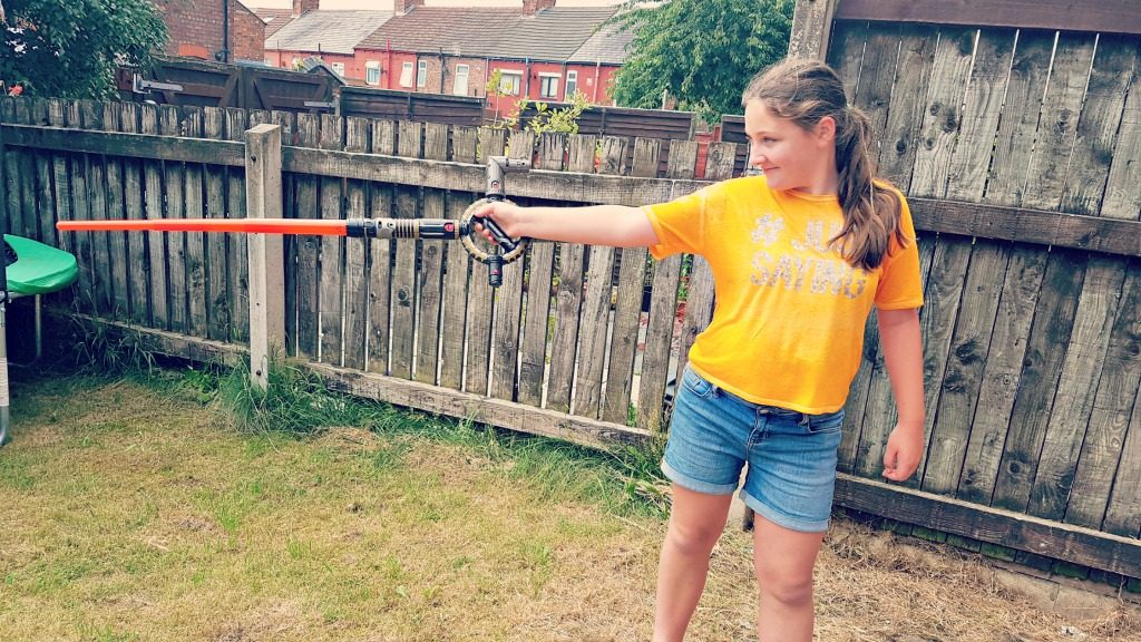 young girl on an oragne top and denim shorts standing on a grassy area in front of a fence holding a starwars lightsabre