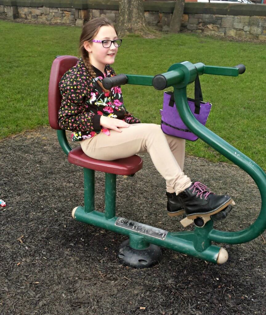 safe-flooring-for-children-outside-girl-on-exercise-bike-in-park