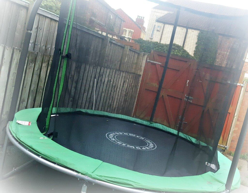trampoline with safety net in a back garden