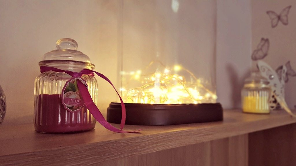 led firefly lights lit on a shelf with candles