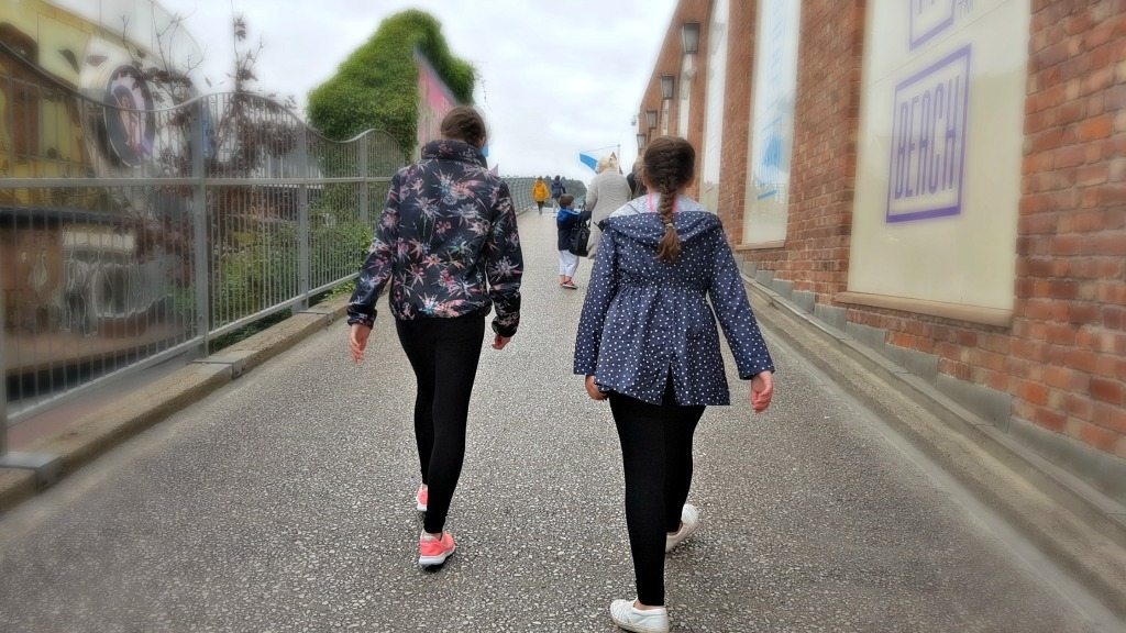 back of 2 girls walking away wearing black leggings and rain jackets