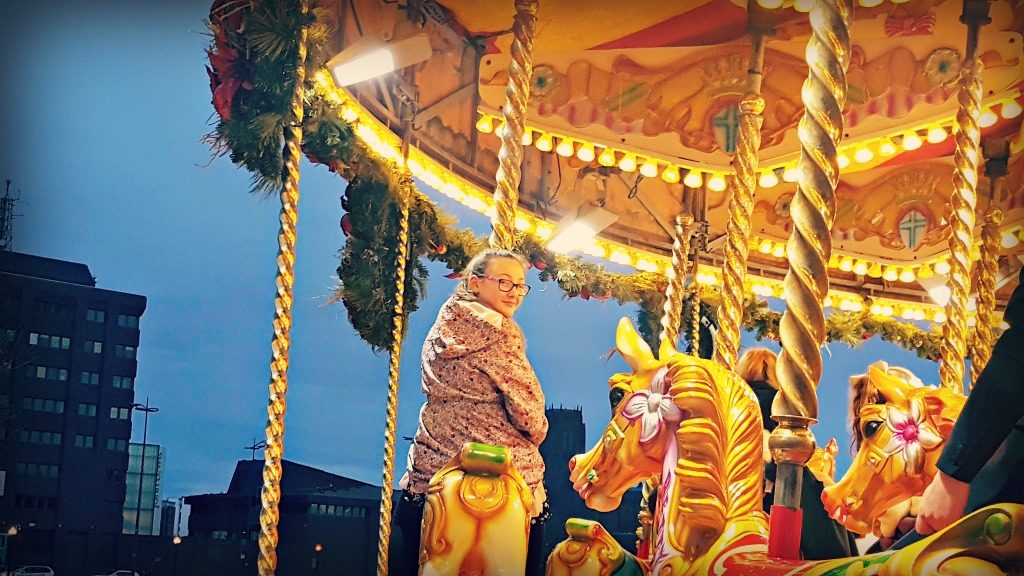 girl on carousel for winter traditions seeing a panto