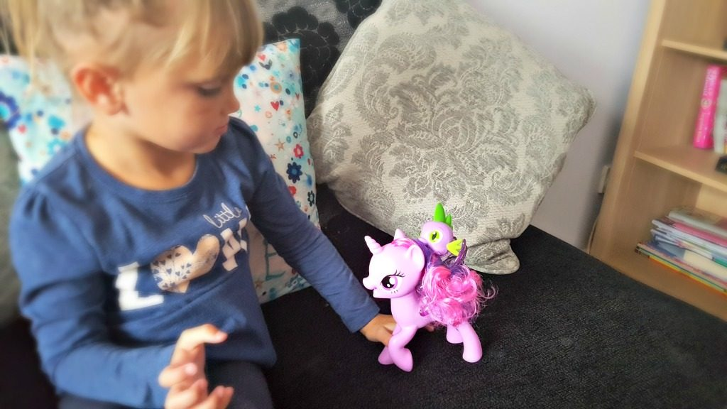 girl playing with a my little pony twilight sparkle and spike the dragon playset