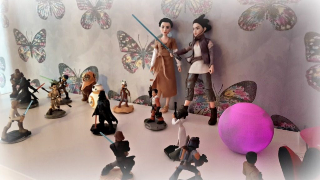 princess leia organza figure with rey of jakku figure with small star ward figures around them and a butterfly wallpaper background
