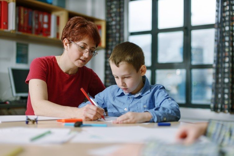 teaching assistant - woman teaching a young boy