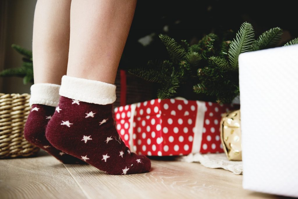 feet in front of a christmas tree