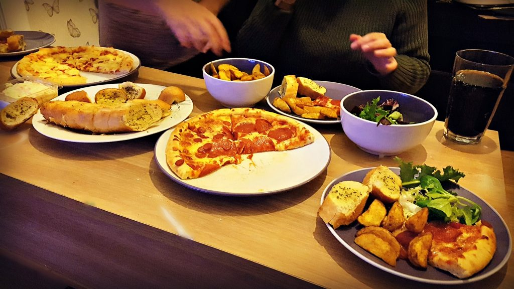 family meal help yourself with an array of different pizzas and other food