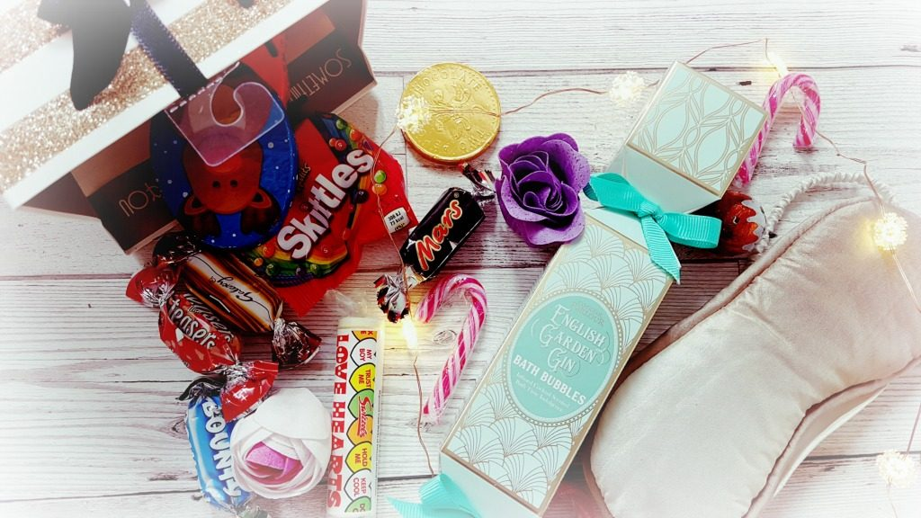 christmas gift bags with sweets, chocolates, bath products and an eye mask