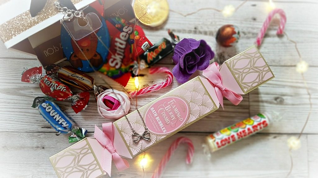 a selection of sweets, chocolates, bubble bath and a silver bow ted baker necklace with led lights in christmas gift bags