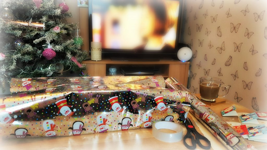 presents being wrapped in christmas theme paper in front of christmas tree and tv