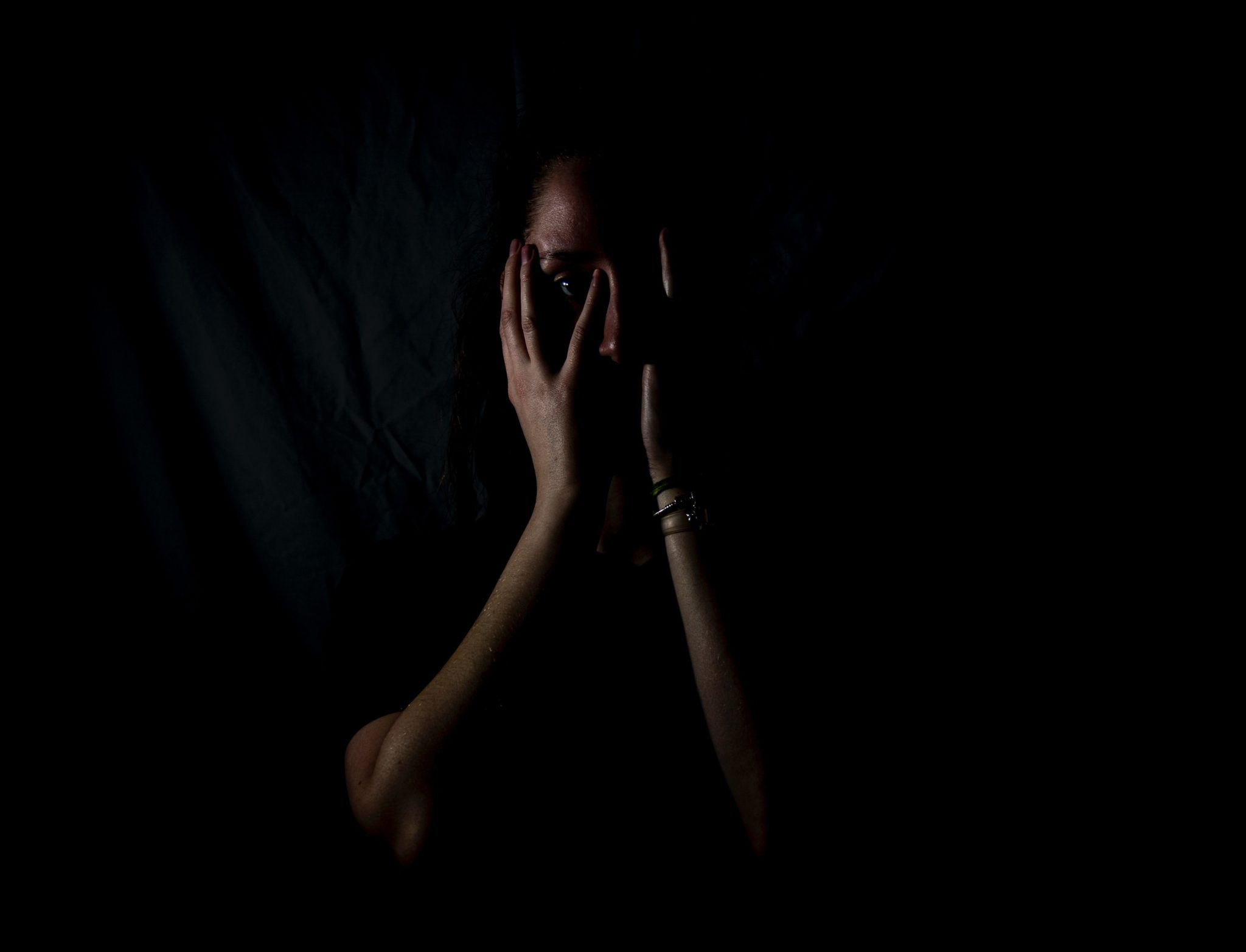 woman in the dark with hands in front of face