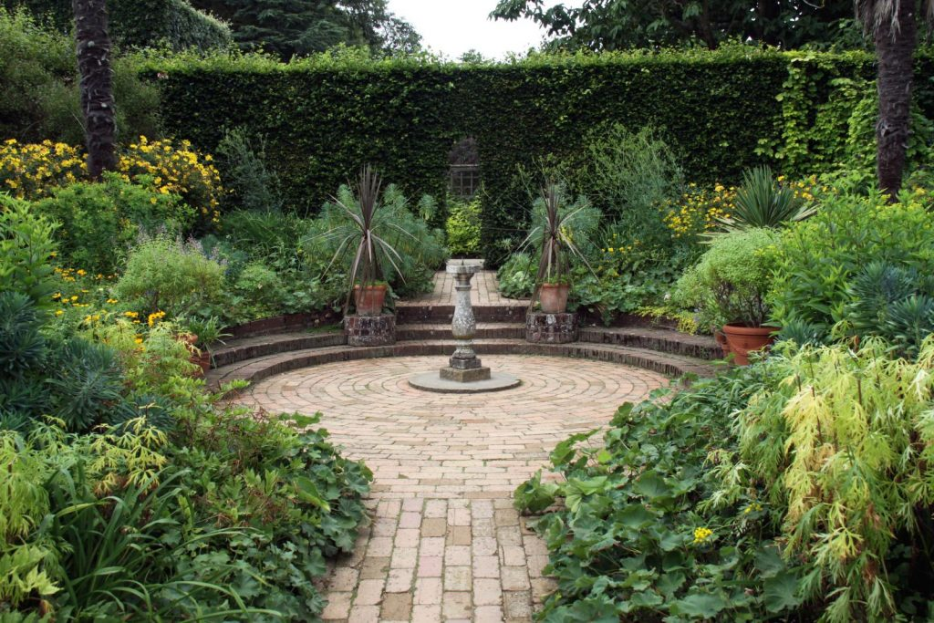 an amazing garden with shubbery around a circle patio feature with a water fountain in the centre