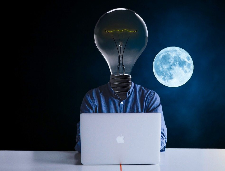 man sat at a macbook on a desk with a moon behind him and a lightbulb for a head for a post on creative inspiration