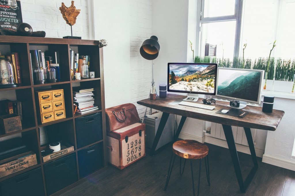 home office in front of a window with shelving with books and accessories and 2 screens on the desk with an industrial style lamp in the corner