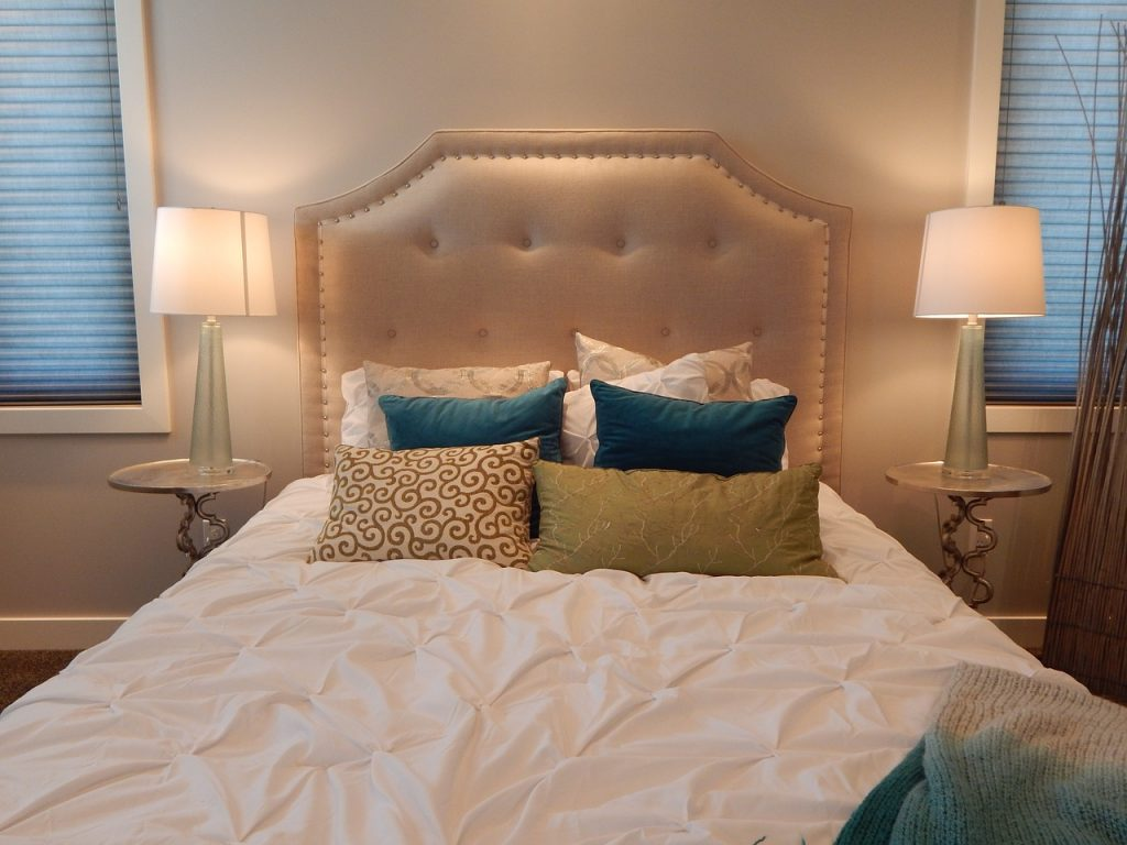 messy bed with padded headboard and scatter cushions