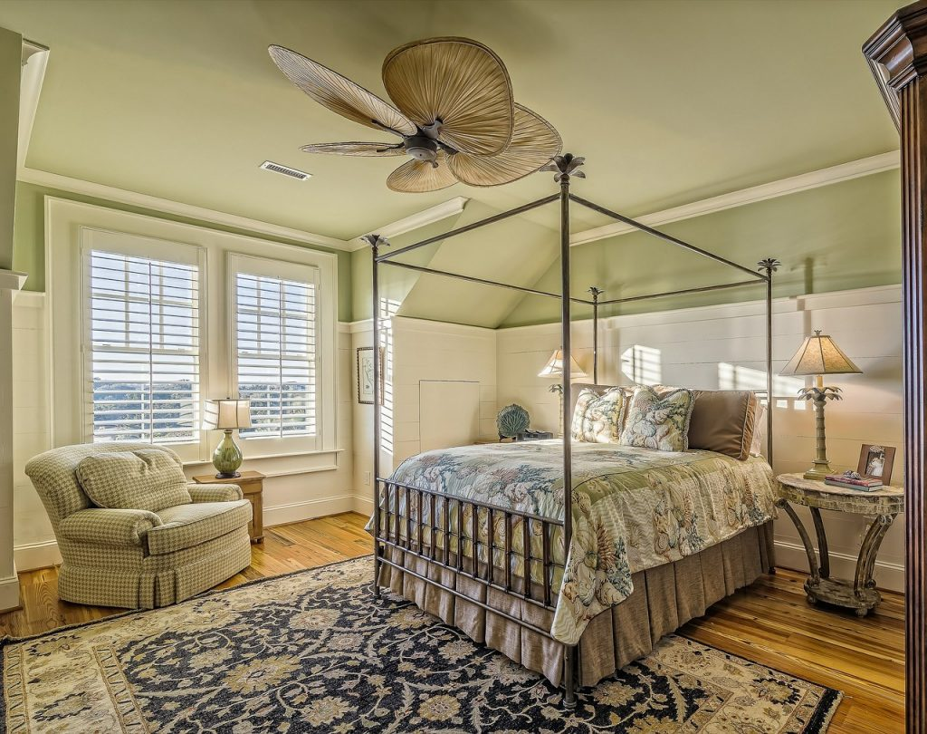 heavy patterned bedroom with four poster bed and armchair with ceiling fan and rug