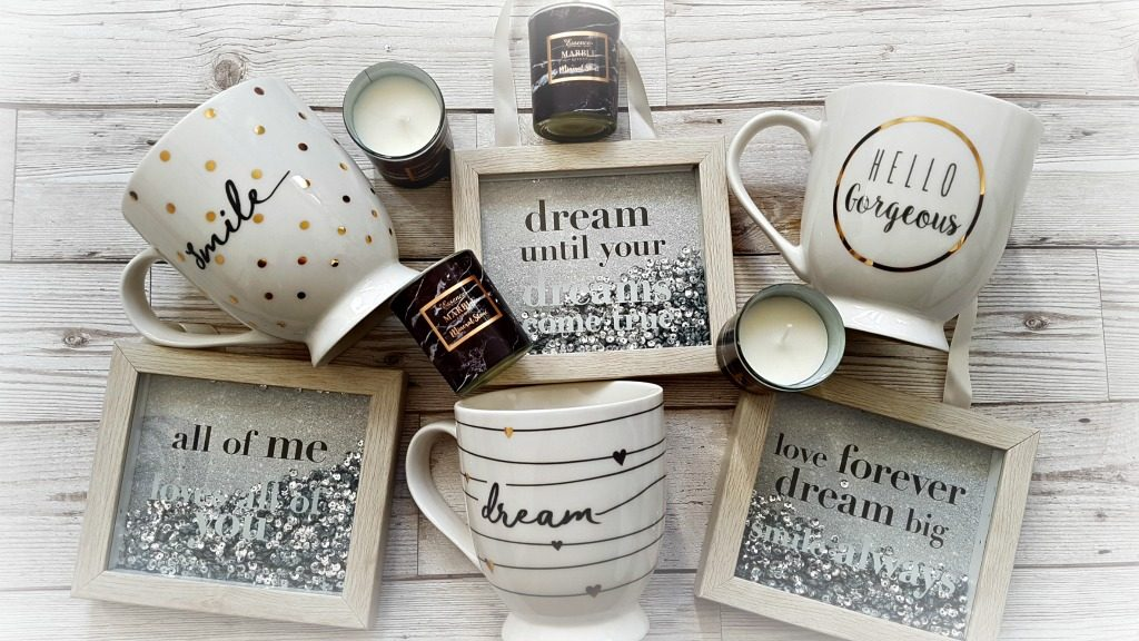 3 sequin wooden frames with quotes, 3 mugs with words on and 4 small glass candles on a wood background from the mothers day range at b&m