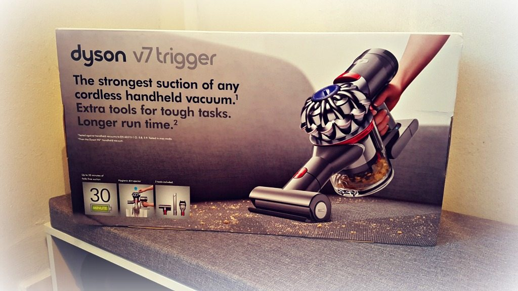 a box image of a dyson v7 trigger on a grey cushion on a white unit