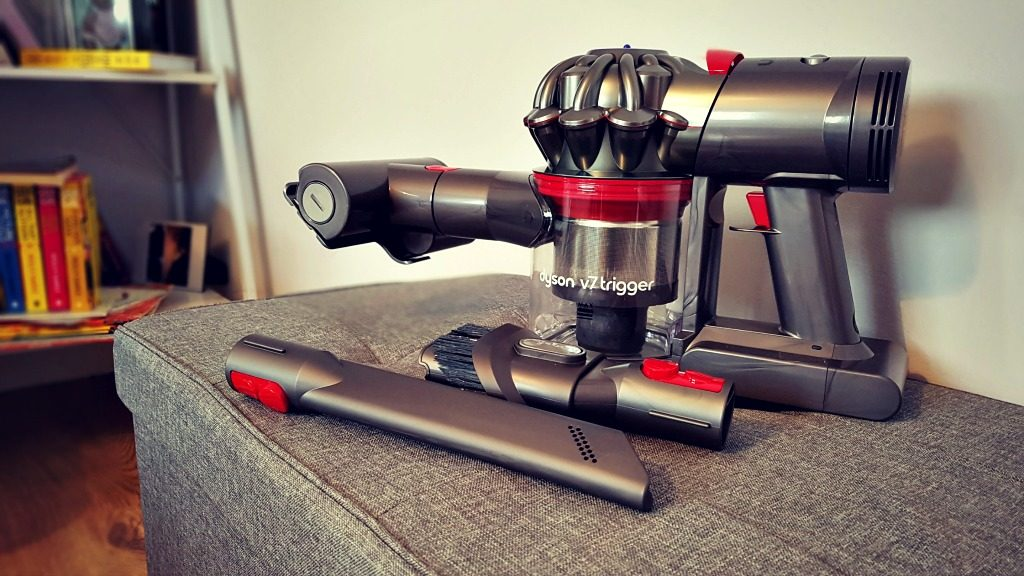 dyson v7 trigger set up on a grey unit in front of a bookcase showing all the tools you get with the vacuum