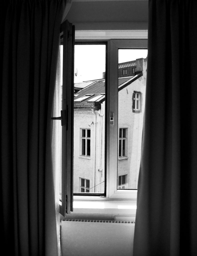 black and white image of an open double glazed window and heavy curtains open at the side of the windows