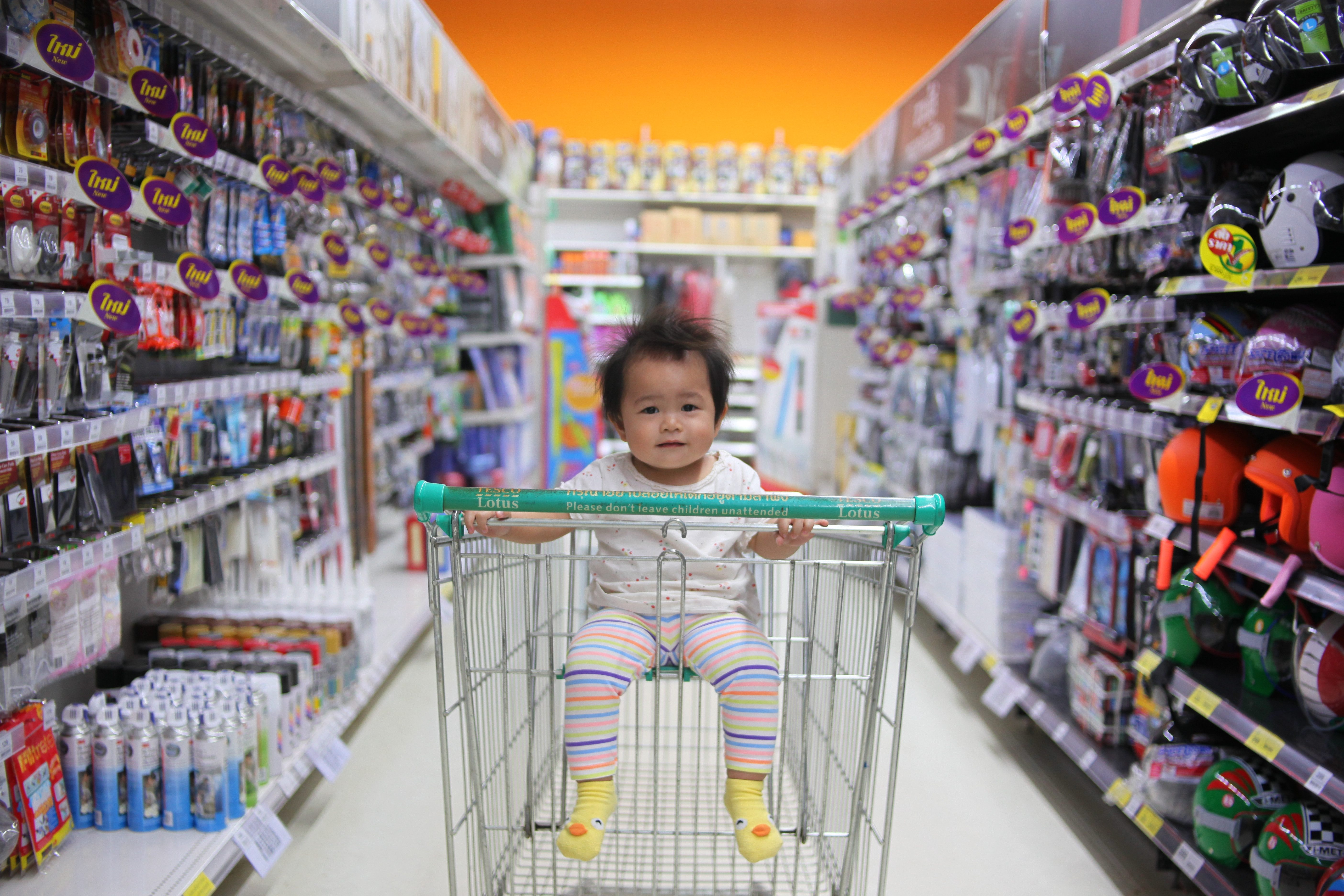 baby sat in a trolley seat in a store aisle