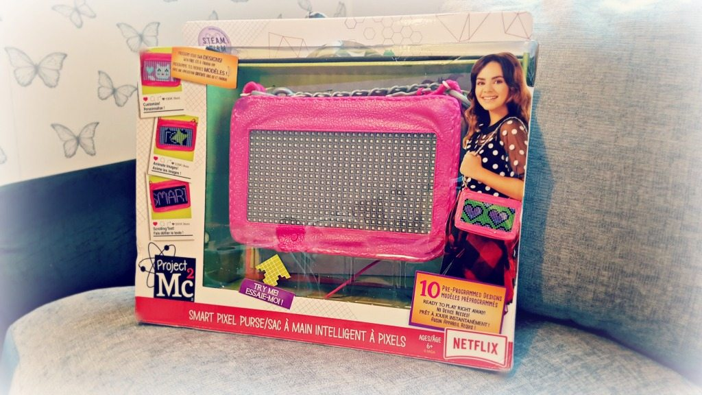 mc2 pixel purse in box on a silver background