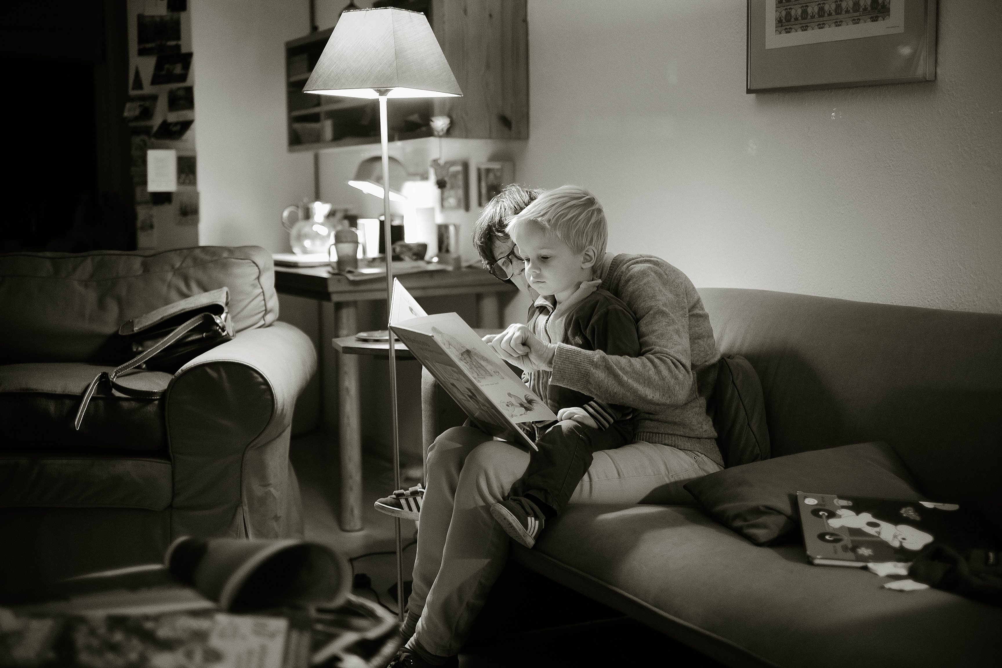 adult and child sat on a sofa reading in a black and white image