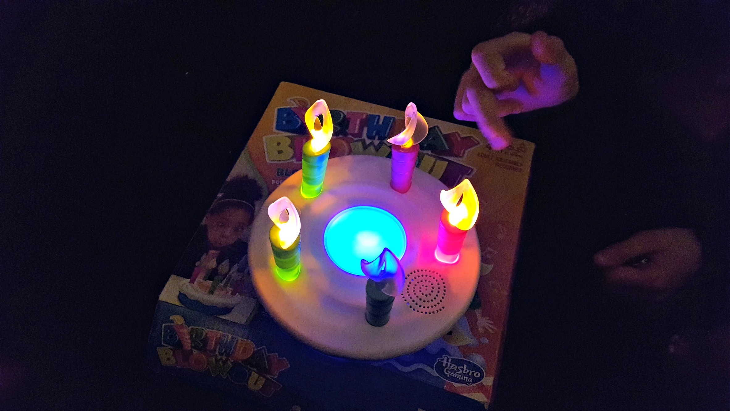 hasbro birthday blowout game on box in the dark with candles and cake lit up