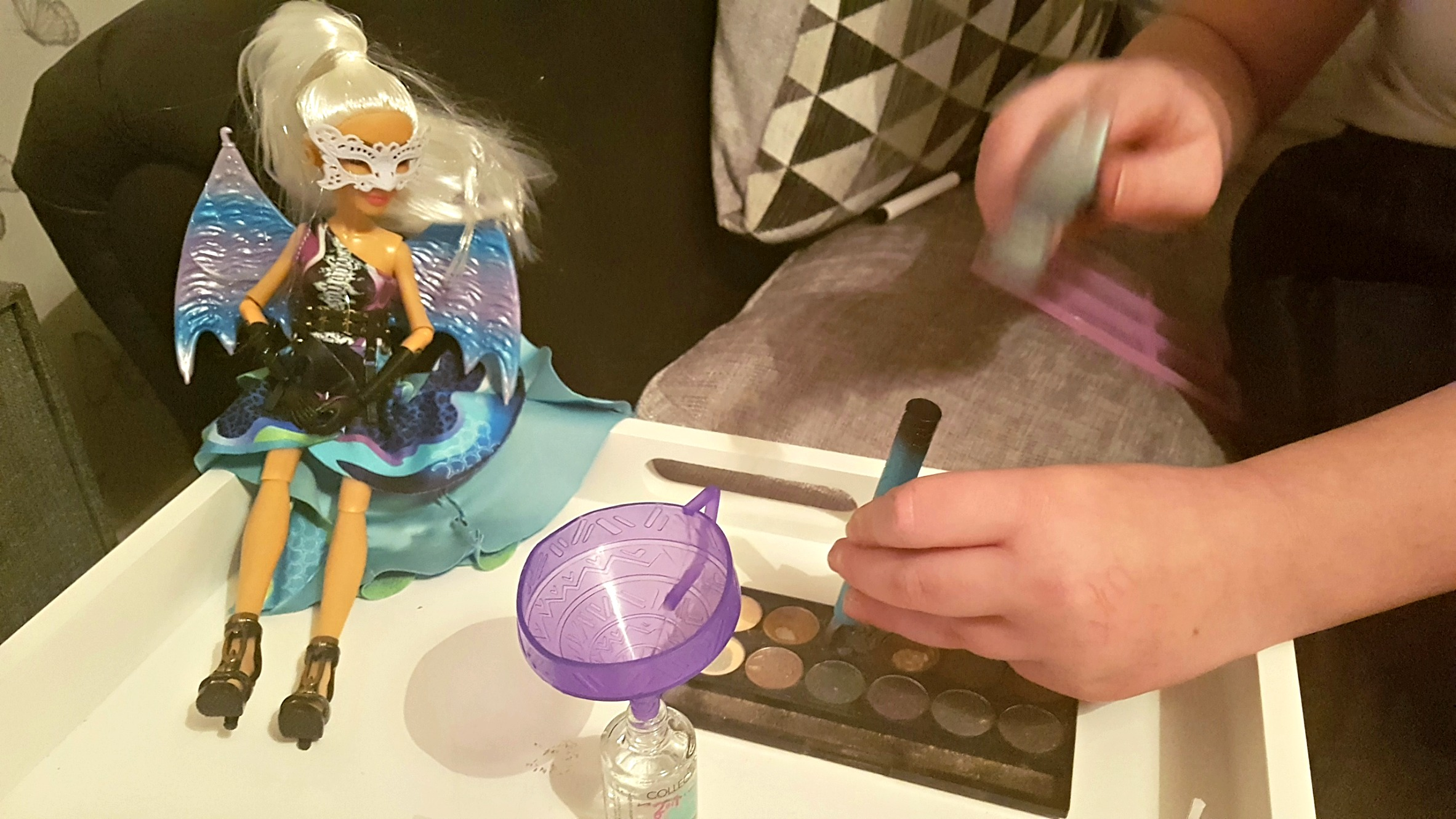 project mc2 experiement doll camryn and girl using a plastic hammer on eye shadow