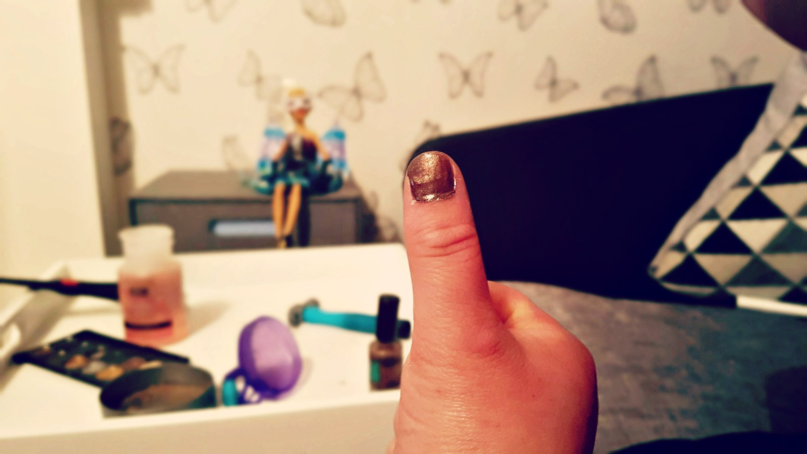 thumb with brown coloured nail varnish with a doll and makup blurred in background
