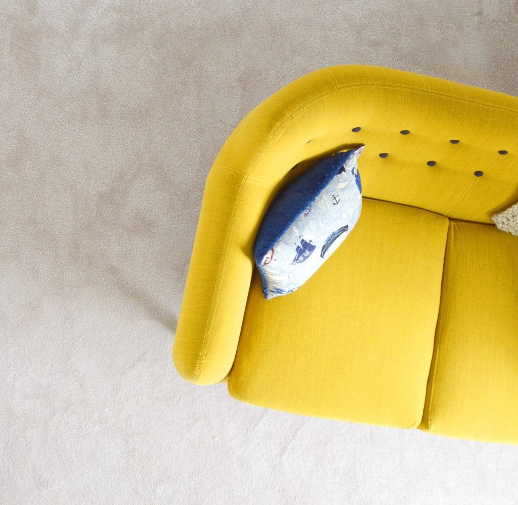 part of a yellow sofa with a blue nautical cushion on a grey floor