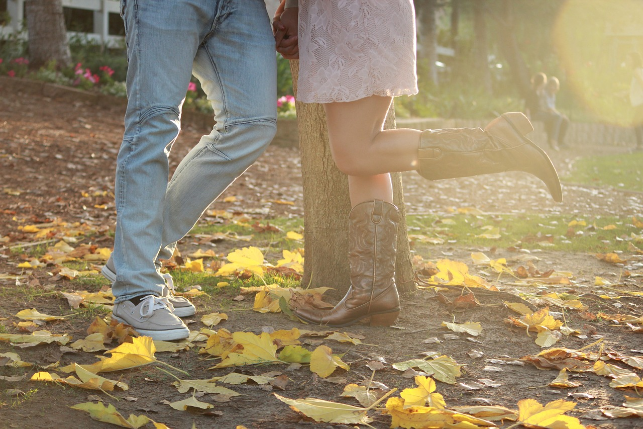legs of a man and woman standing in front of a tree with leaves on the ground