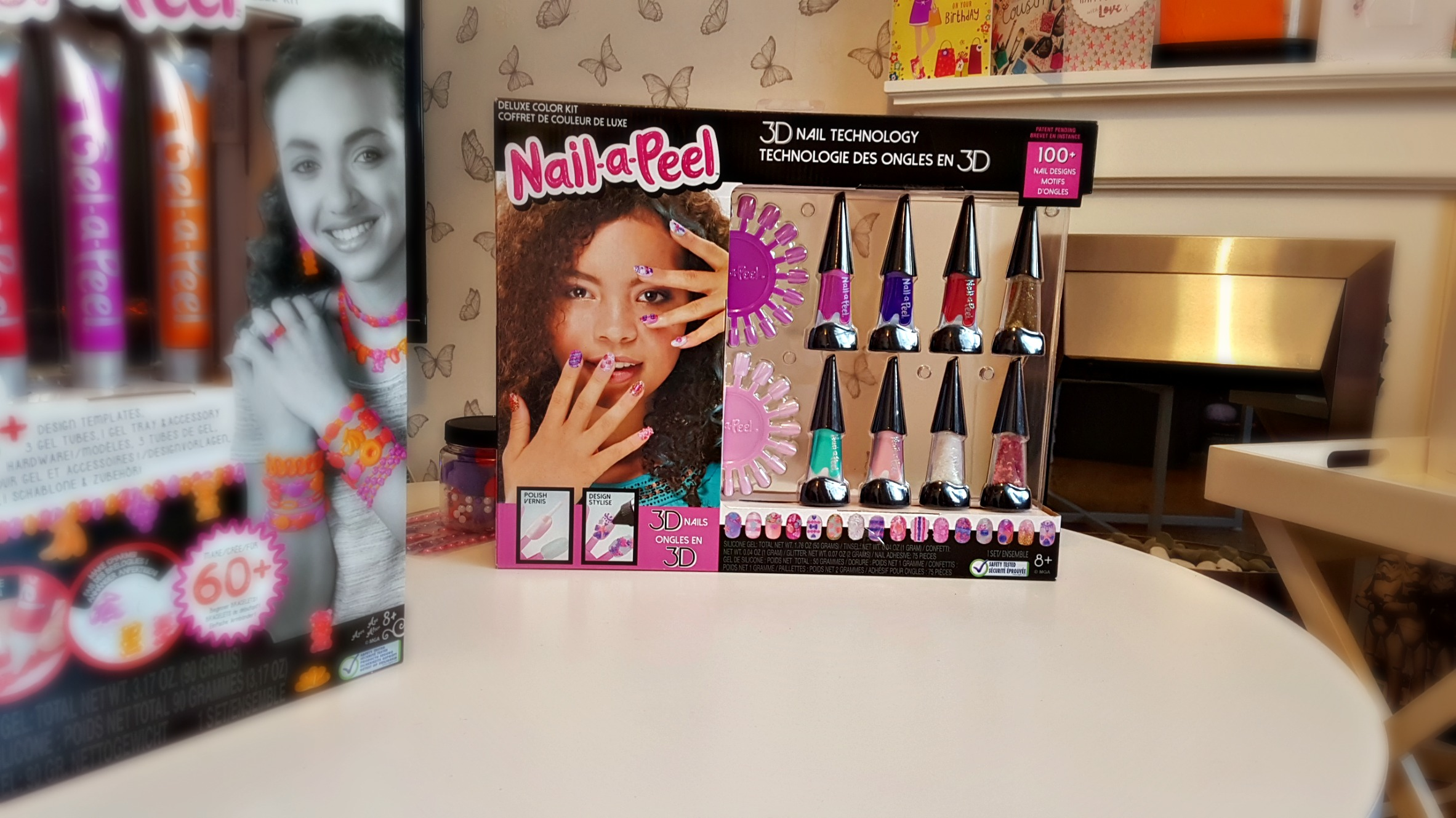 box of nail-a-pell deluxe set on a whitw table in front of a fireplace