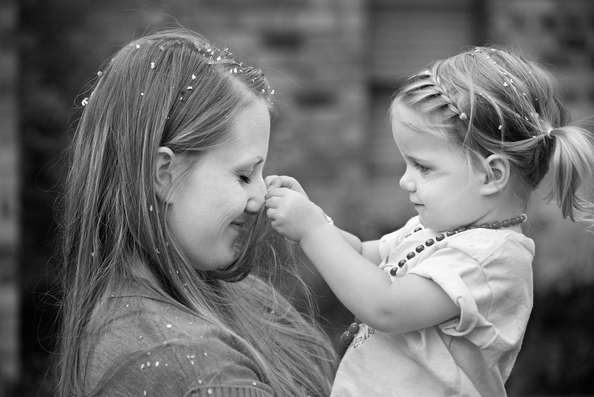 woman holding young girl who is pulling her nose