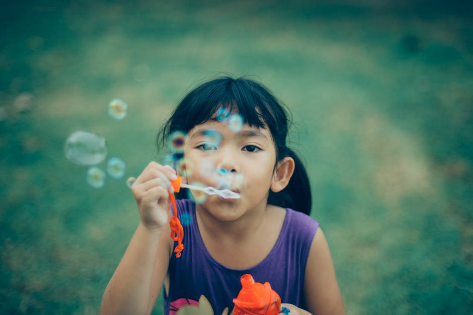 young girl blowing bubbles in a garden