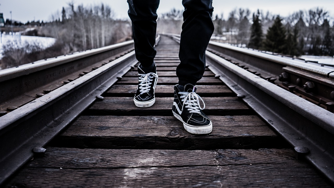 black sneakers on feet walking on railway line