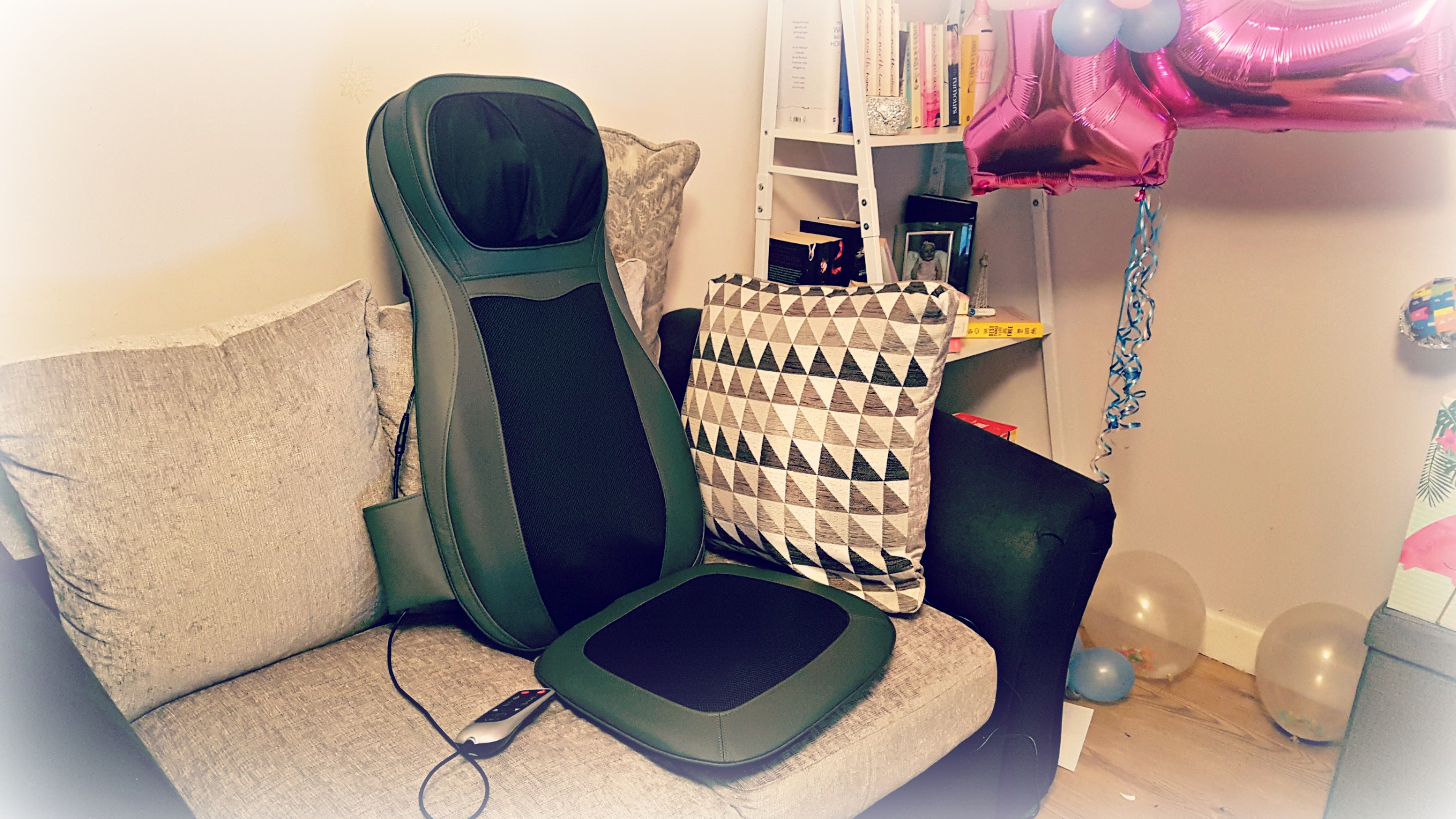 naipo back massager on a grey sofa with birthday items in the background