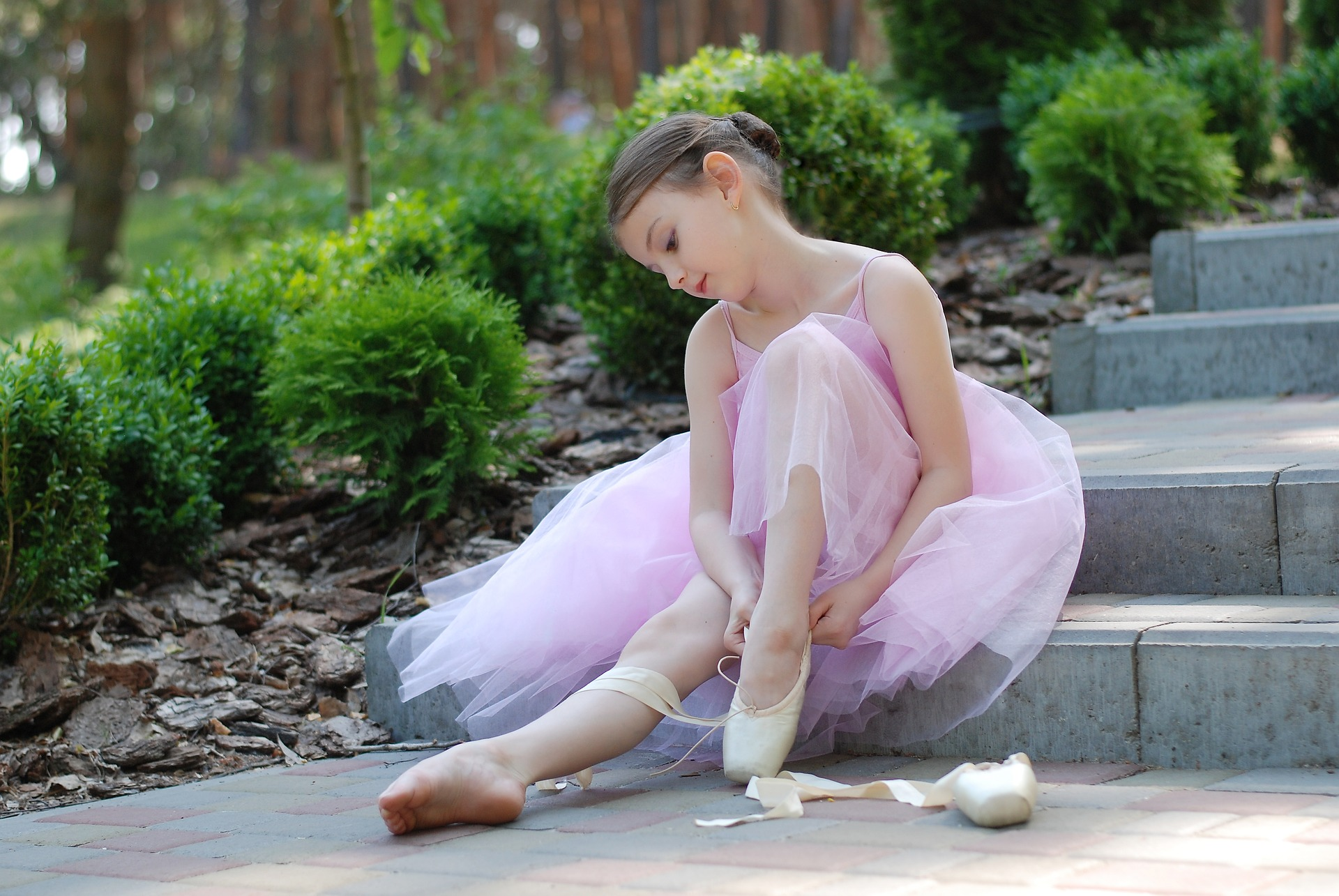 young girl in a ballerina outfit sitting on steps putting her pumps on